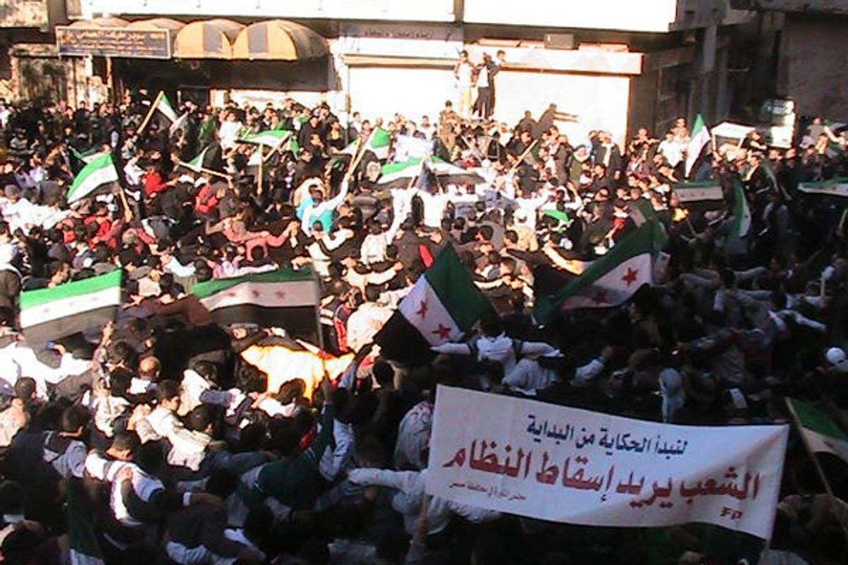 """Demonstrators protesting against Syria's President Bashar al-Assad wave the old Syria flag as they march through the streets on the first day of the Muslim festival of Eid-al-Adha in Alsnmin near Daraa November 6, 2011. The banner reads, """"People want the regime to step down"""".         (Reuters)"""