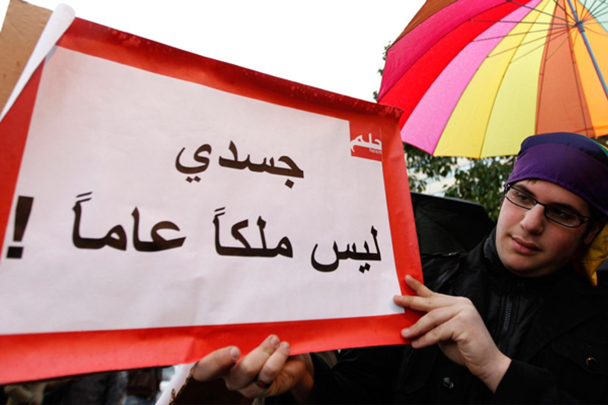 """A protester carries a banner that reads in Arabic, """"My body is not public property"""" during a sit-in for gays and lesbians in Beirut. (AP/Hussein Malla)"""