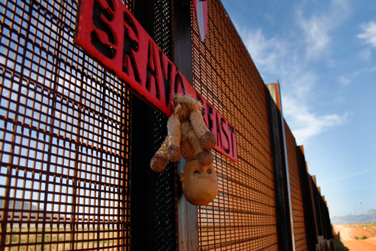 A toy doll hangs from the U.S. and Mexico border fence in Naco, Arizona September 7, 2011  (Reuters/Joshua Lott)