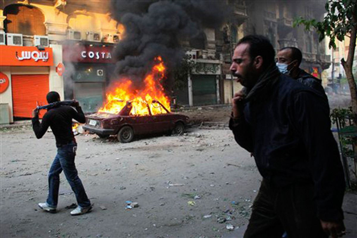 Protesters move away from tear gas fired by Egyptian riot police during clashes near Tahrir Square in Cairo on Monday.  (AP/Tara Todras-Whitehill)