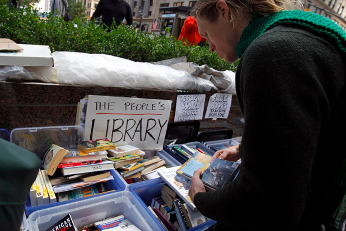 A demonstrator browses books at the library of the Occupy Wall Street protesters' camp at Zuccotti Park in lower Manhattan in New York October 3, 2011.     (Mike Segar / Reuters)