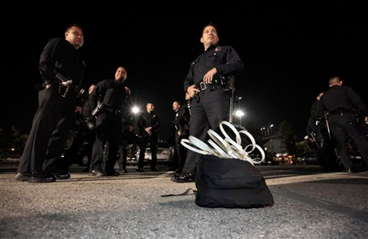 Los Angeles police officers stand by a sack containing wrist restraints late Tuesday, as they prepare to evict protesters from the Occupy Los Angeles encampment outside City Hall.   (AP/Lucy Nicholson)