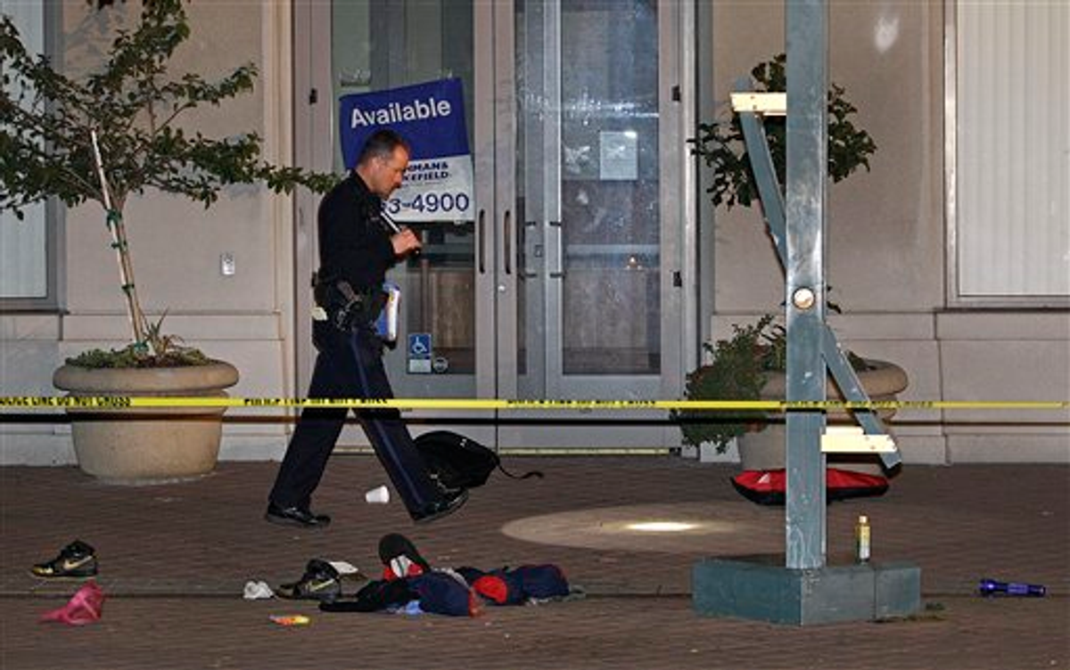 A police officer investigates the scene where a man was shot and killed Thursday, Nov. 10, 2011, in Oakland, Calif   (AP Photo/Ben Margot)