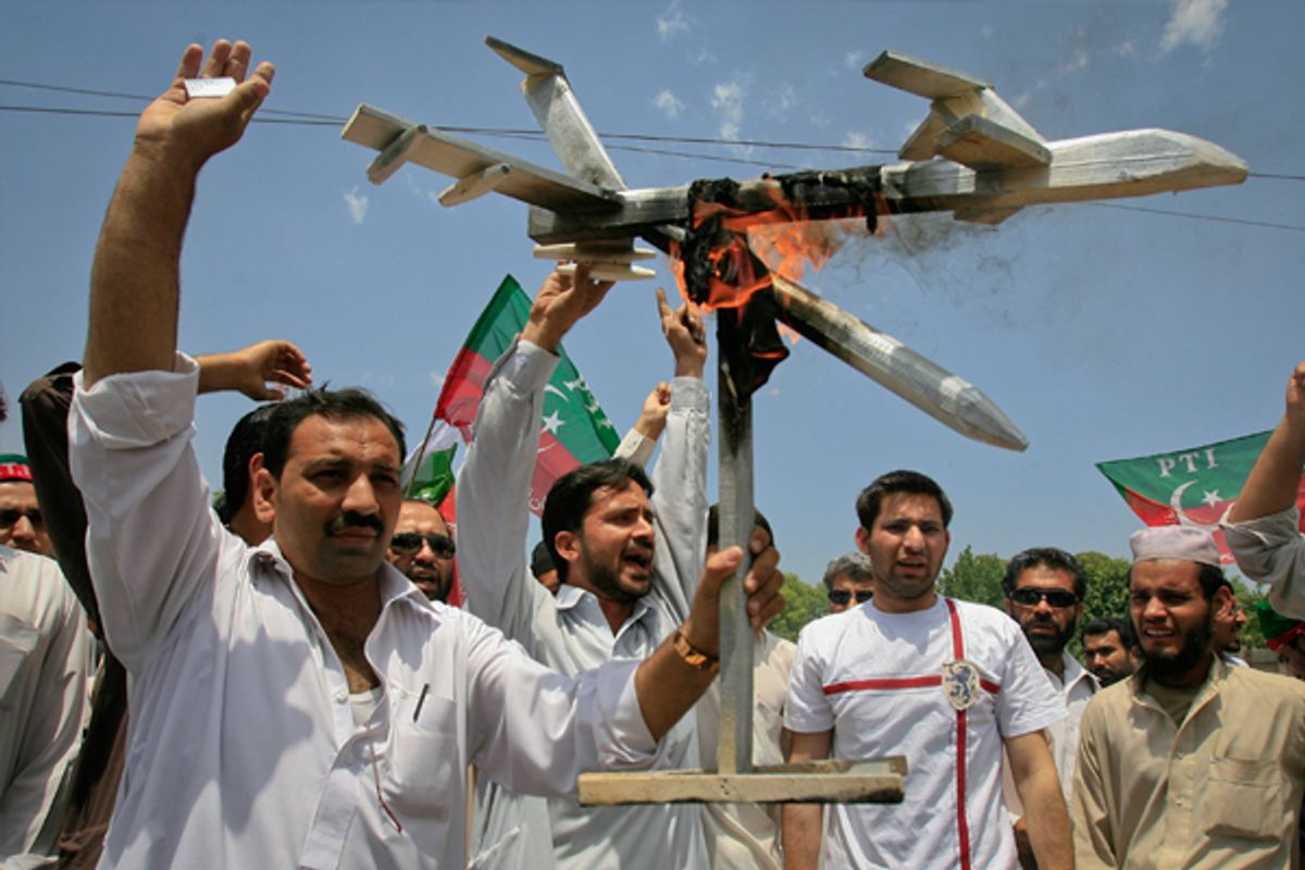 Protesters hold up a burning mock drone aircraft during a rally against drone attacks in Pakistan.         (Reuters/K. Pervez)