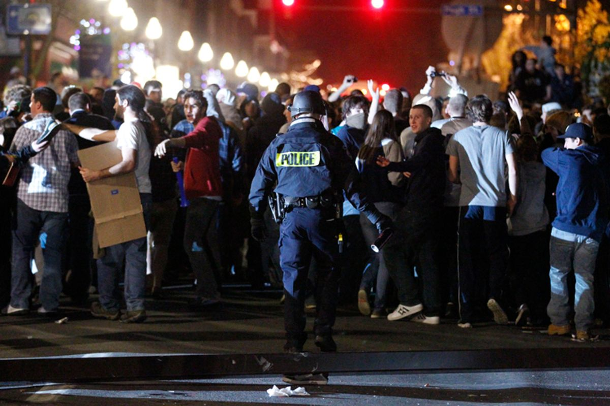Police hold back students after they reacted off campus Nov. 10, 2011, in State College, Pa., to firing of football coach Joe Paterno.     (AP/Matt Rourke)