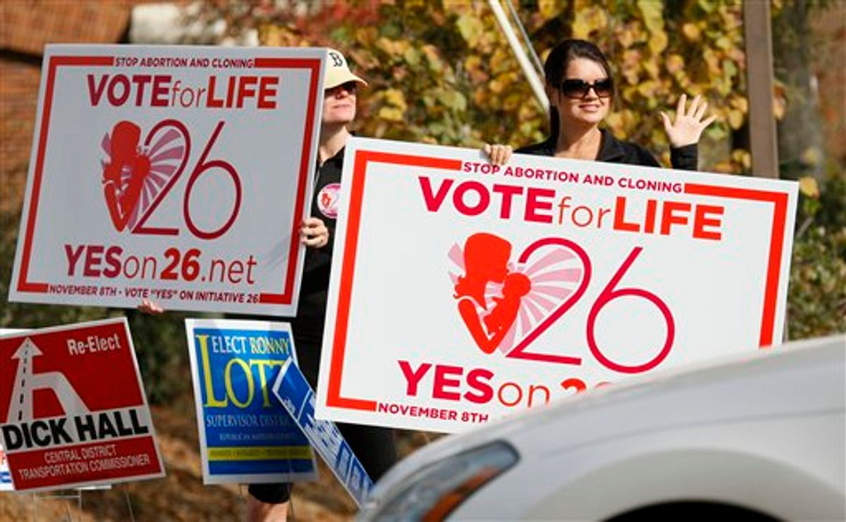 Christi Chandler, left, and Stacy Hawsey, both of Madison and supporters of the Personhood Amendment promote their initiative as they waver signs at drivers in the midst of last minute campaigning Tuesday, Nov. 8, 2011 in Madison, Miss. (AP Photo/Rogelio V. Solis)    (AP)