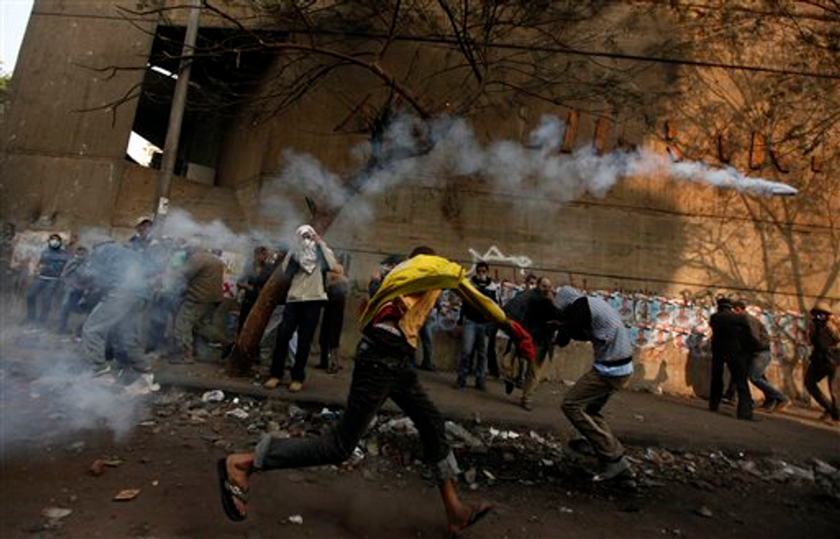 A protester throws a tear gas canister away during clashes with the Egyptian riot police near Tahrir square in Cairo, Egypt, Tuesday, Nov. 22, 2011    (AP Photo/Khalil Hamra)