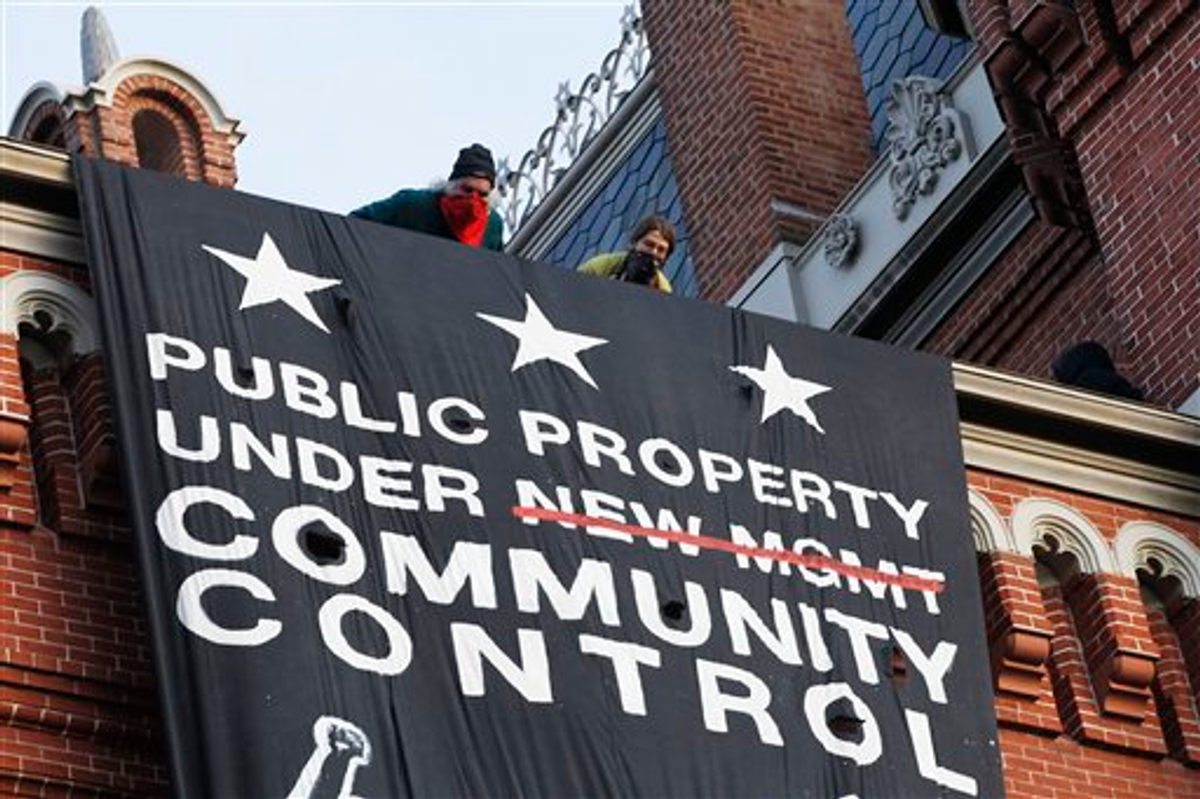 A group of protesters inspired by Occupy D.C. protest hang a banner on Franklin School building, in Washington, Saturday, Nov., 19, 2011   (AP Photo/Pablo Martinez Monsivais)