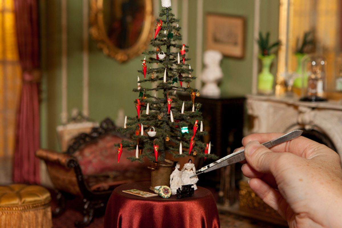 Thorne Rooms caretaker Lindsey Mican Morgan adjusts tiny decorations in a miniature Victorian English drawing room. (The Art Institute of Chicago)