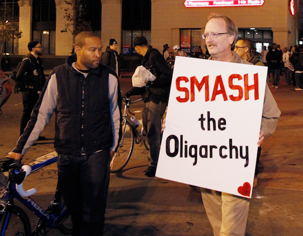 A demonstrator holds up his sign as he marches to City Hall plaza in Oakland, Calif. November 14, 2011     (REUTERS/Kimberly White)