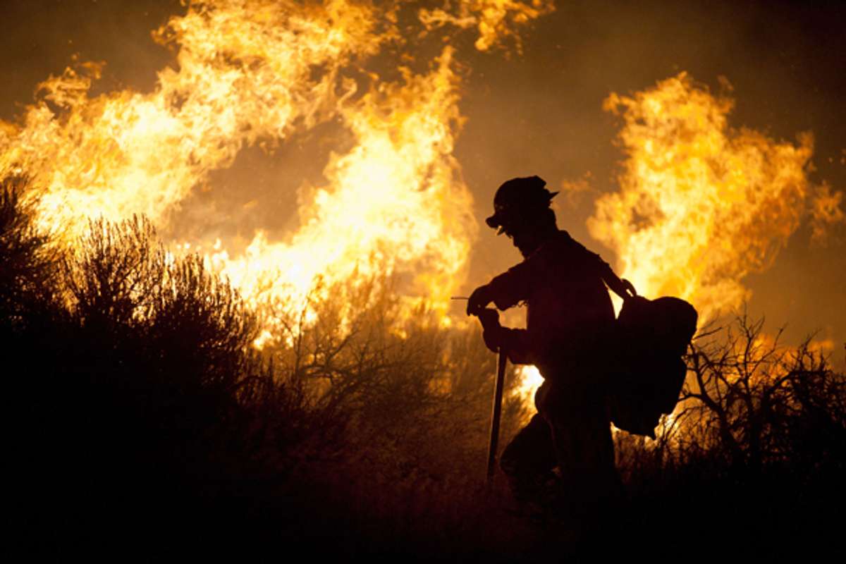 A crew member from the Nevada Department of Forestry works to control the Washoe Drive fire in Washoe City, Nev. on January 19, 2012     (Reuters/James Glover II)