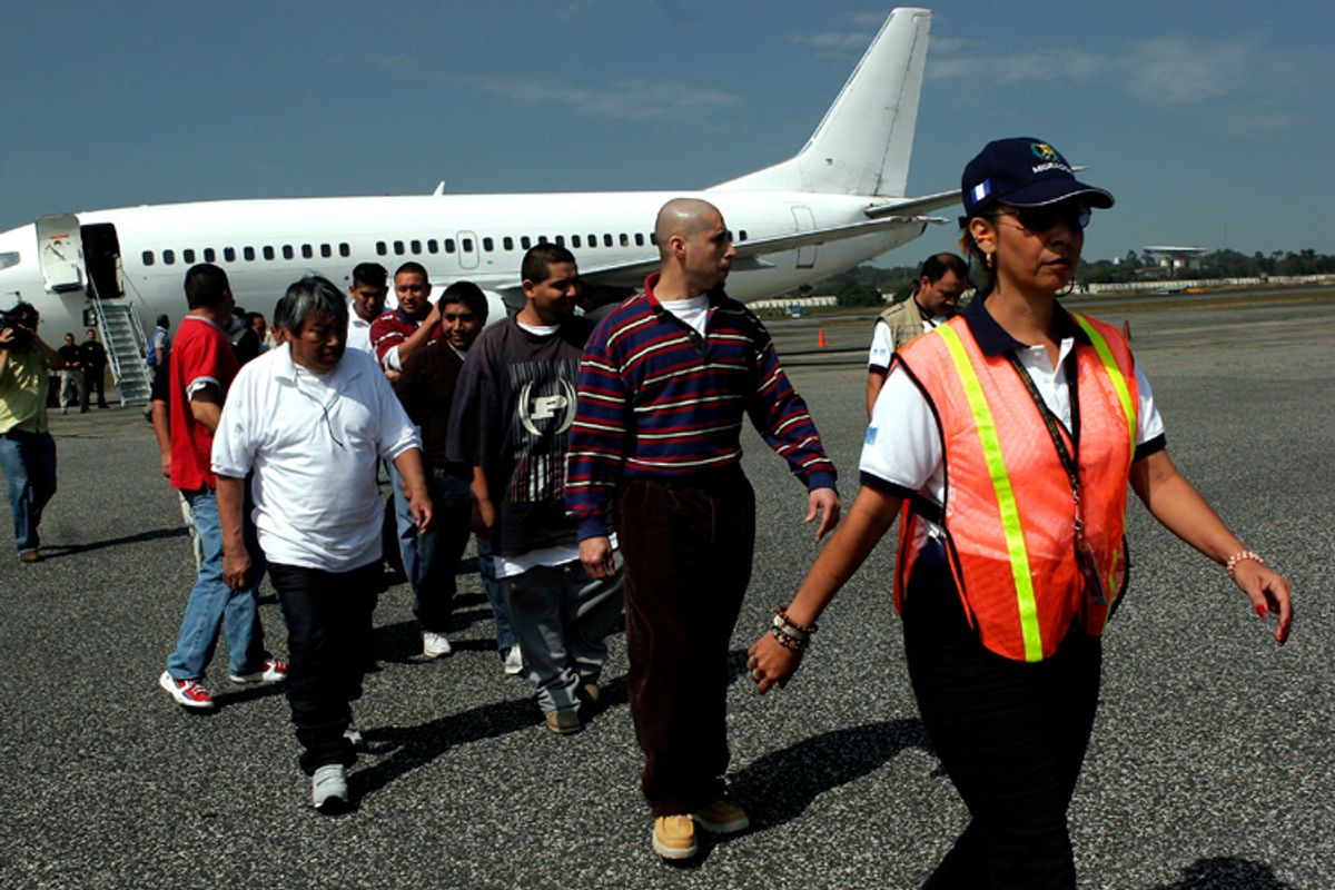 Guatemalans deported from the United States are escorted by an immigration official upon their arrival at La Aurora International Airport in Guatemala City.       (AP/Moises Castillo)