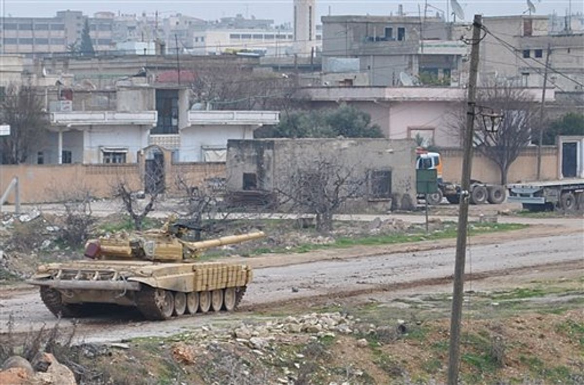 A Syrian forces tank moves along a road during clashes with the Syrian army defectors, in the Rastan area in Homs province, central Syria, on Monday Jan. 30, 2012.      (AP)