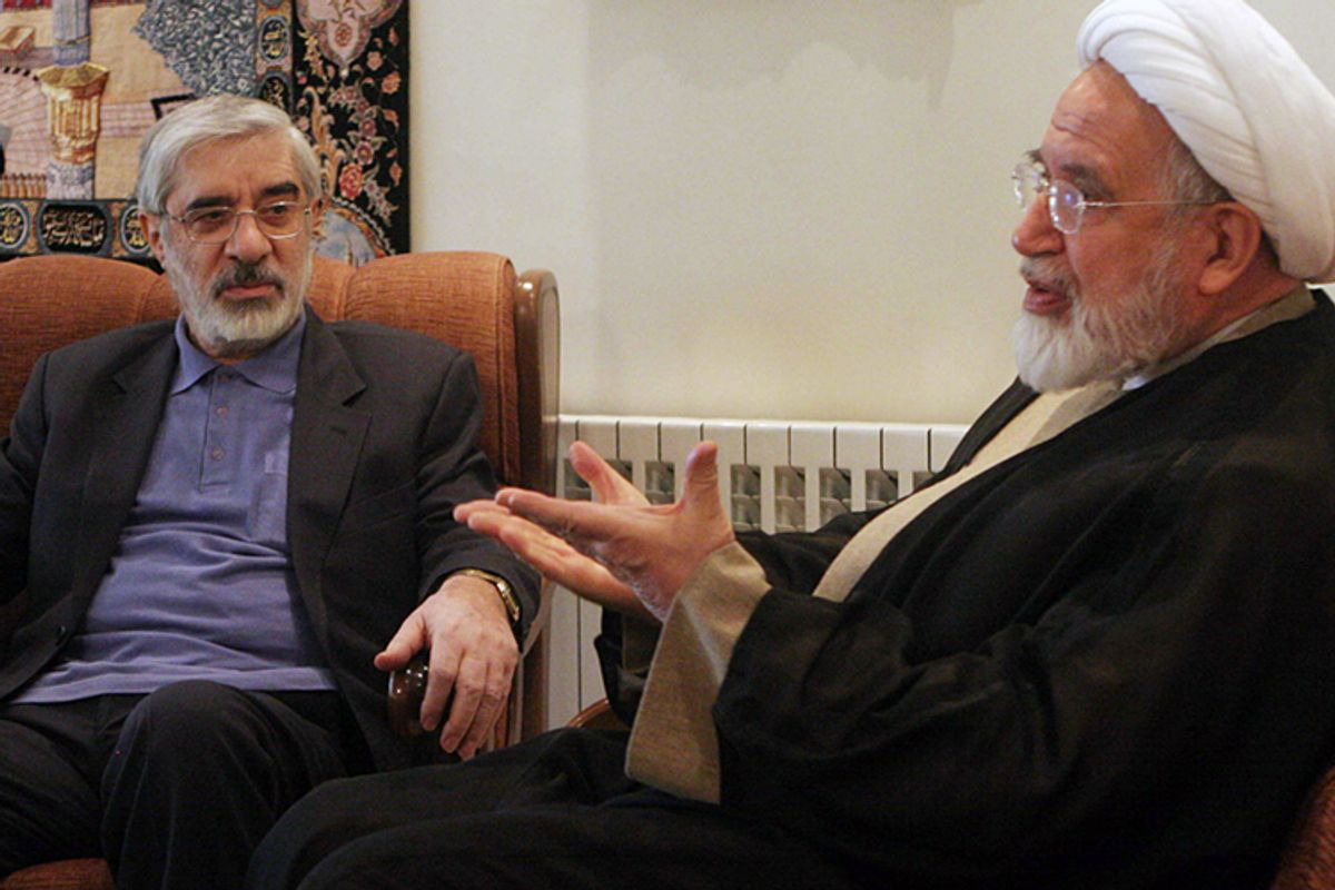 The now-confined leaders of Iranian opposition, Mahdi Karroubi, right, and Mir Hossein Mousavi, talk in freer days in Tehran.      (AP)