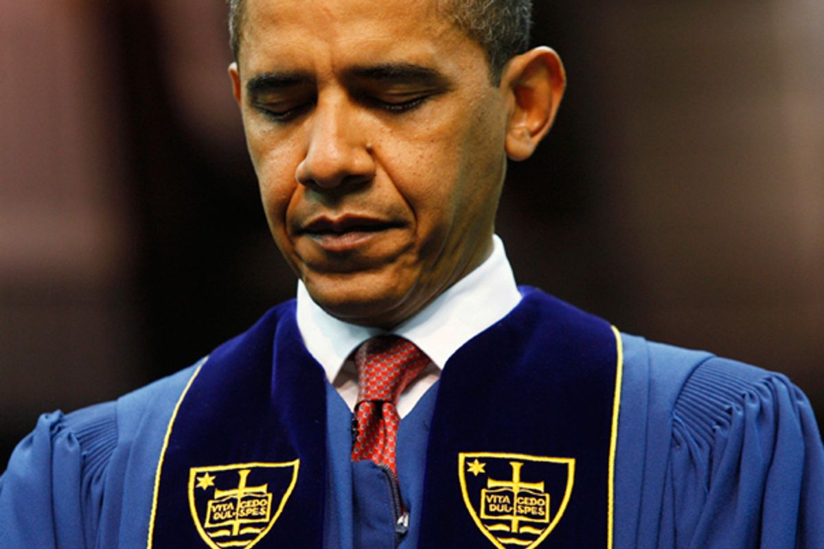President Obama bows his head in prayer prior to speaking at the University of Notre Dame during commencement ceremonies in 2009.        (AP)
