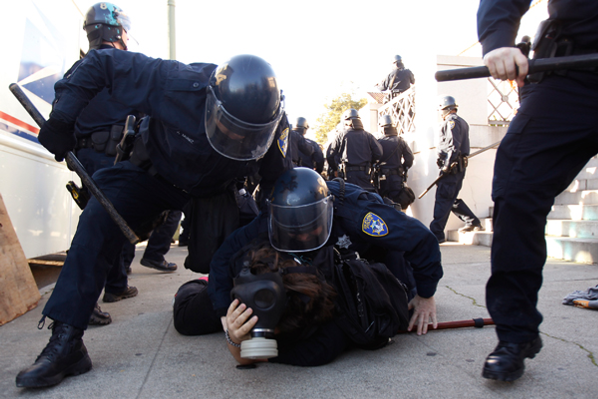 Members of the Oakland Police Department arrest an Occupy Oakland demonstrator in Downtown Oakland, California January 28, 2012        (Reuters/Stephen Lam)