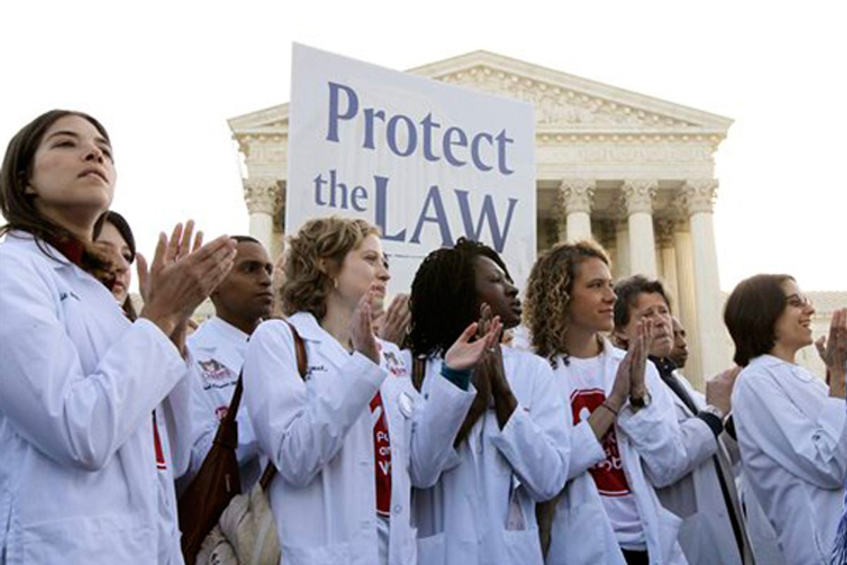 Doctors and medical students supporting President Obama's health care reform law gather in front of the Supreme Court on Monday.              (AP/Charles Dharapak)