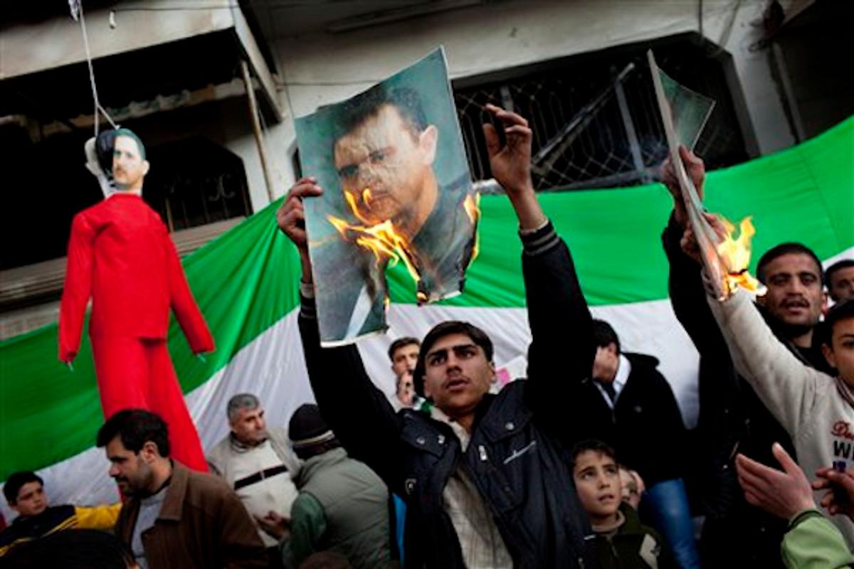 Protesters burn portraits of Syrian President Bashar al-Assad in northern Syria on Feb. 26, 2012           (AP Photo/Rodrigo Abd)