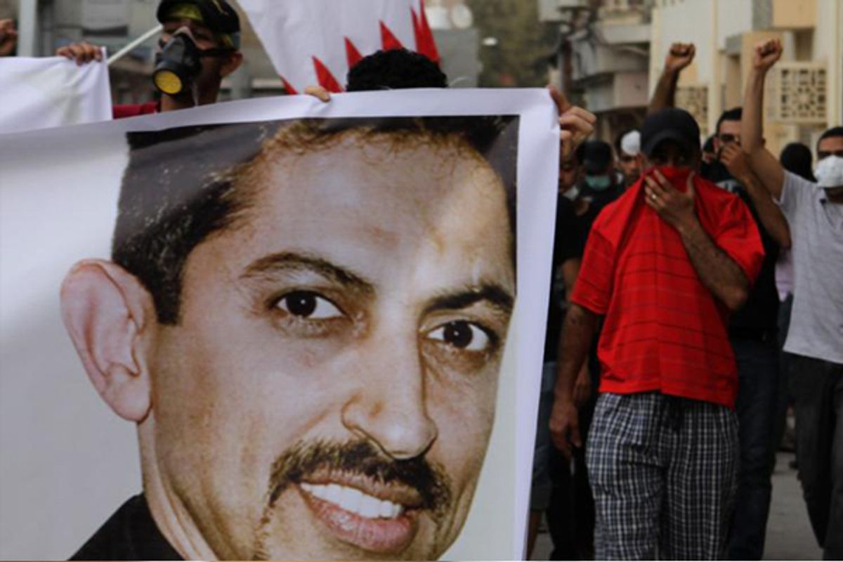 Bahraini anti-government protesters, protecting their faces from tear gas, carry national flags and a picture of jailed human rights activist Abdulhadi al-Khawaja at a protest on ApPril 4.     (AP/Hasan Jamali)