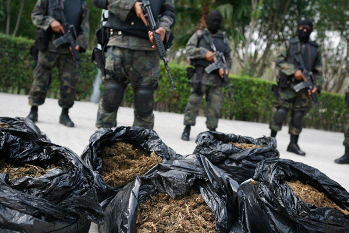 Soldiers stand guard next to bags of marijuana being displayed to the media at a military base on the outskirts of Monterrey, Mexico.        (Reuters/Tomas Bravo)
