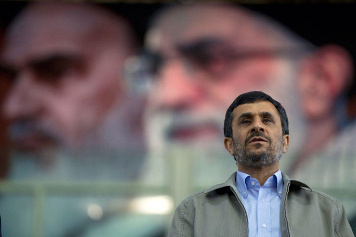 Iran's President Mahmoud Ahmadinejad stands beneath a portrait of Supreme Leader Ayatollah Ali Khamenei.        (Reuters/Caren Firouz)