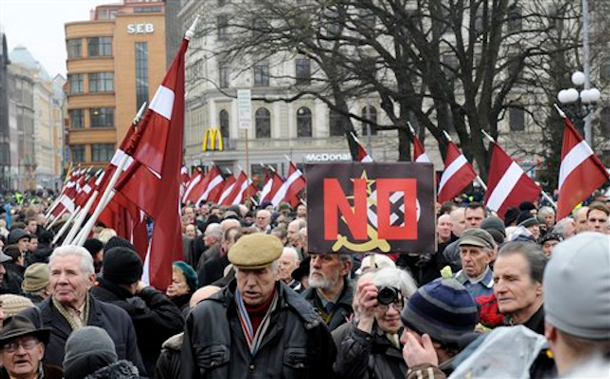 With Latvian flags, people march in a procession to honor soldiers who fought in a Waffen SS unit during World War II, in Riga, Latvia, Tuesday, March 16, 2012   (AP Photo/Roman Koksarov)