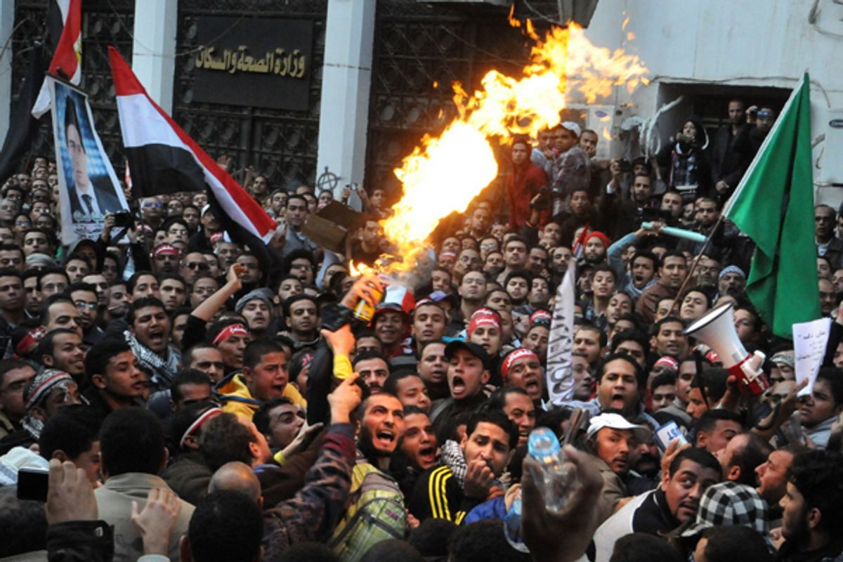 Egyptian protesters, left, spray burning aerosol over Muslim Brotherhood guards outside the Egyptian parliament.      (AP)