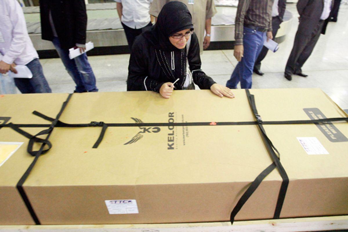 Fatima Alhimidi weeps over her mother Shaima Alawadi's coffin as it arrives in Najaf, Iraq.     (AP/Alaa al-Marjani)