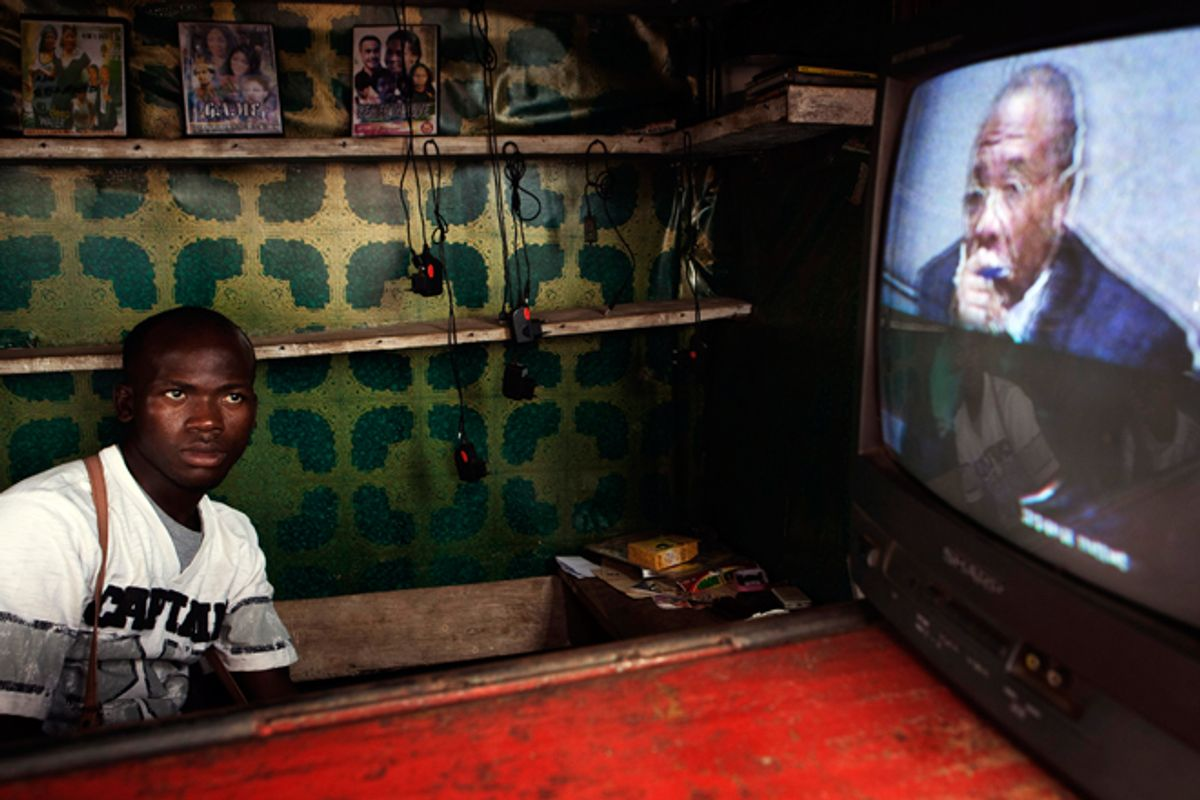A Freetown street vendor watches a live broadcast of the  Taylor verdict being delivered.    (Reuters/Finbarr O'Reilly)