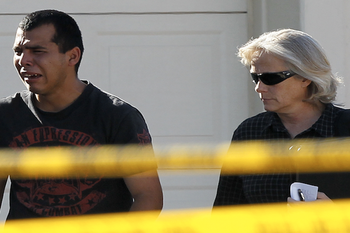 A police officer walks with a man who said he had a child inside of the home where five people were shot Wednesday, May 2, 2012 in Gilbert, Ariz.    (AP Photo/Matt York)