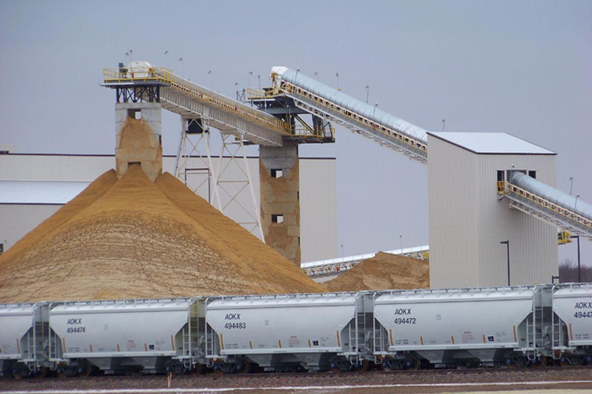 Frac sand piles up at a processing plant in Chippewa Falls, Wis.    (AP/Steve Karnowski)