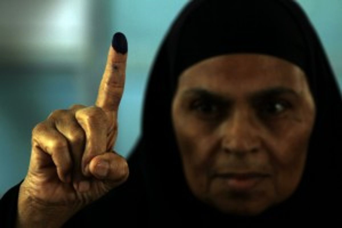 An Egyptian woman shows the ink on her finger after voting in an historic presidential election Wednesday, May 23, 2012, outside a polling station in Cairo, Egypt.      (AP Photo/Hasan Jamali)