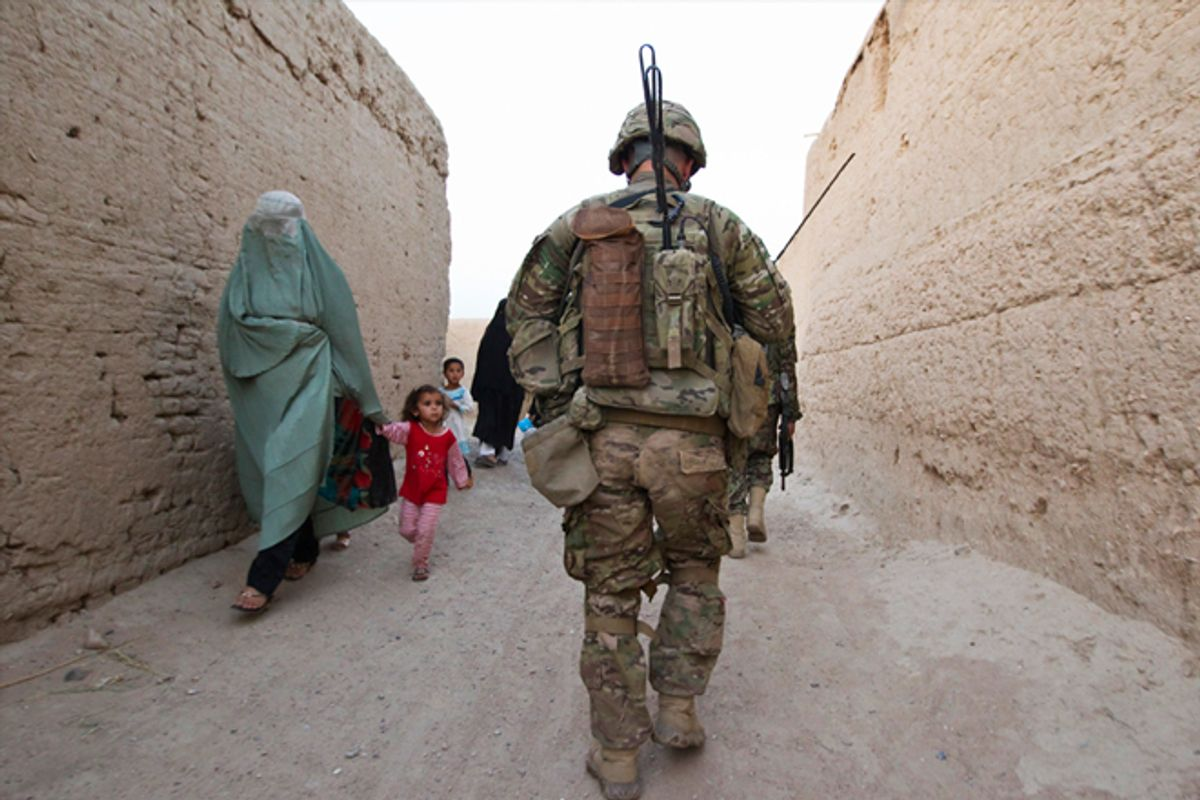 An Afghan family walks past a U.S. Army soldier in the town of Senjaray.                       (AP/Shamil Zhumatov)
