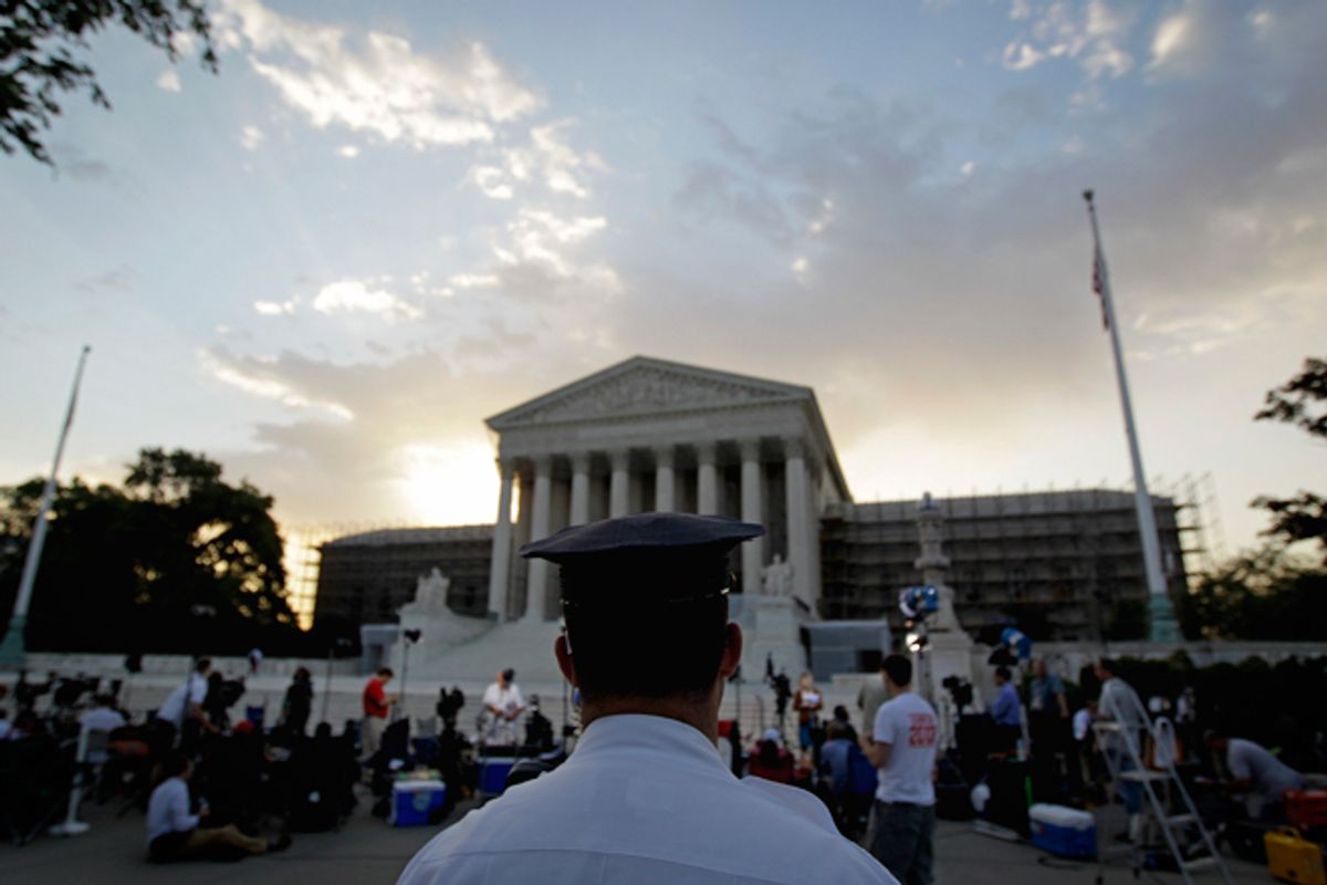 An officer stands outside the Supreme Court as media and the public gather on Thursday.   (AP/David Goldman)
