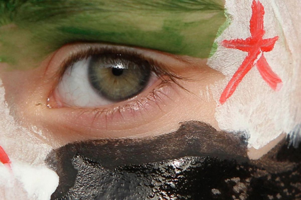 A boy with his face painted in the colours of the Syrian opposition flag takes part in a demonstration against Syria's President Bashar al-Assad.         (Reuters/Ali Jarekji)
