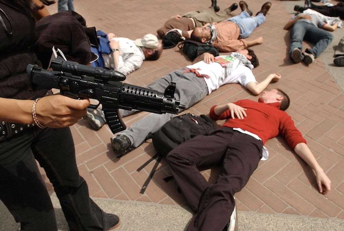 """A protester holding a plastic gun stands over other demonstators with the group """"Students for Justice in Palestine,"""" during a mock """"die-in""""  at the steps of Sproul Plaza, Wednesday, April 9, 2003, on the University of California at Berkeley campus in Berkeley, Calif.  (AP Photo/Ben Margot)"""