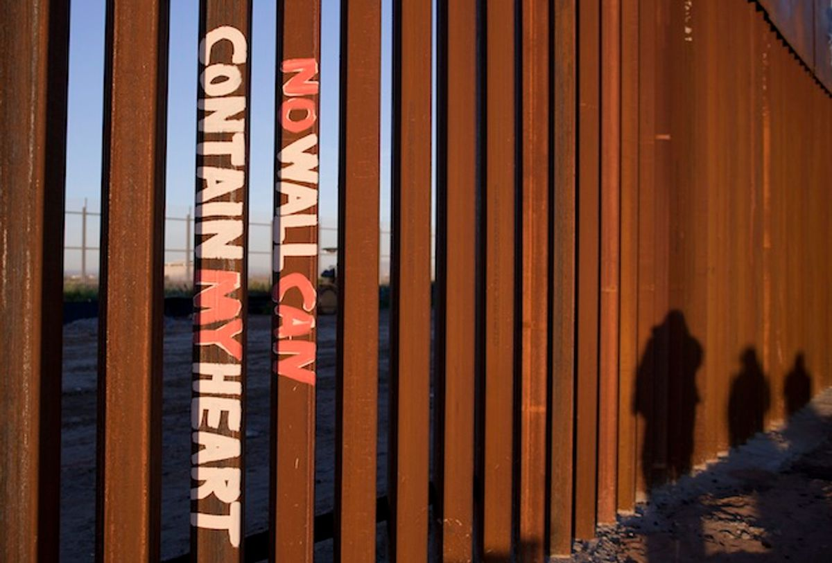 """This Saturday, Jan. 28, 2012 photo shows graffiti reading """"NO WALL CAN CONTAIN MY HEART"""" on the U.S. border fence in Tijuana, Mexico.       (AP/Julie Jacobson)"""