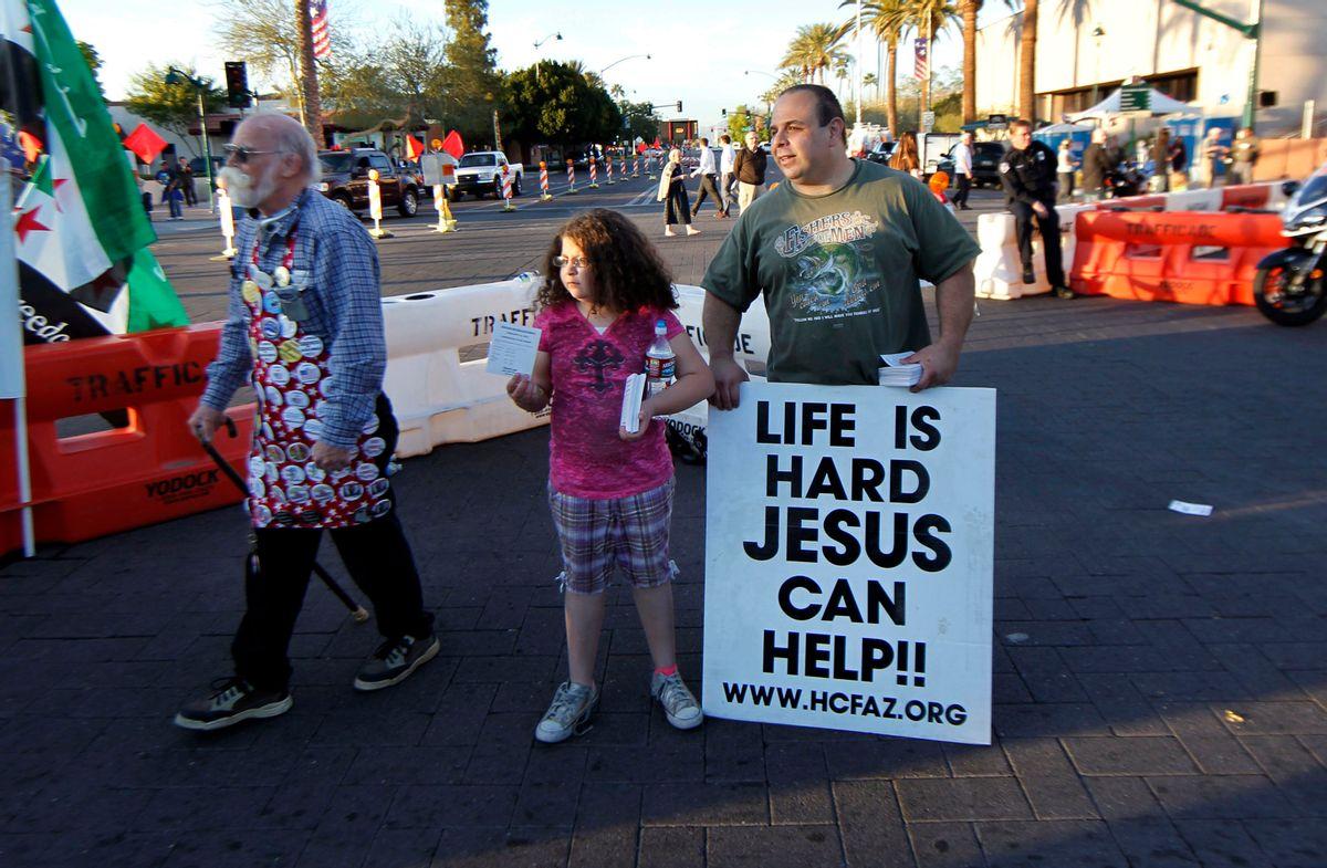 Michael Salman, right, and his daughter Abigail Salman, 8, both of Mesa, Ariz., hand out religious literature in Mesa, Ariz.   (AP/Gerald Herbert)