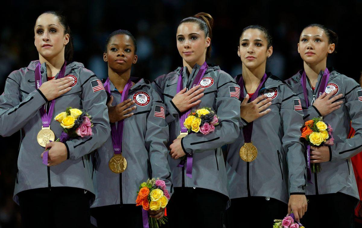 The gold-medal winning American gymnastics team listens to the U.S. national anthem (AP/Matt Dunham)