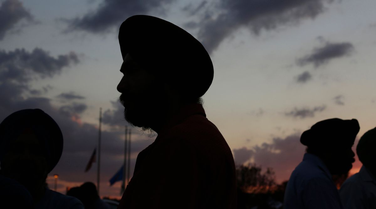 Flags fly at half-staff as Sikhs prepare for a vigil in Oak Creek, Wis., Aug. 7, 2012.     (Reuters/John Gress)