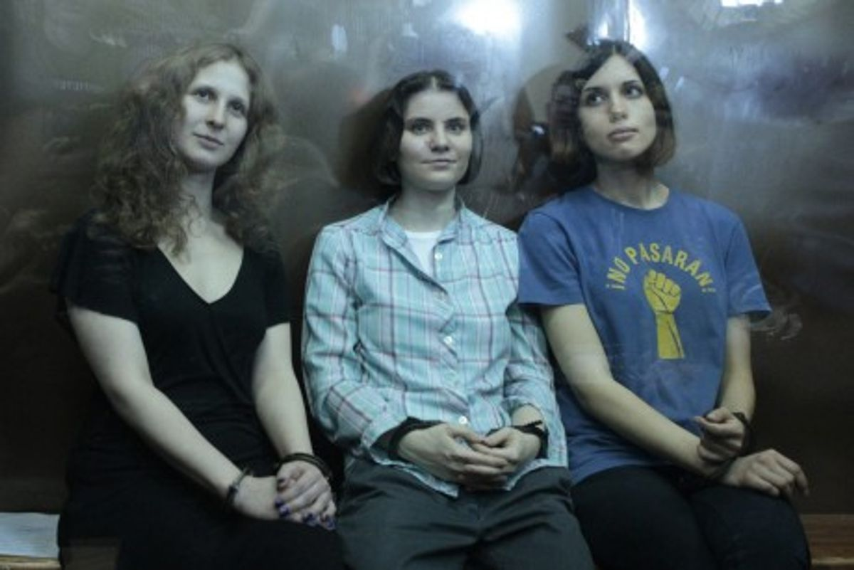 """Members of the female punk band """"Pussy Riot"""" (R-L) Nadezhda Tolokonnikova, Yekaterina Samutsevich and Maria Alyokhina sit in a glass-walled cage after a court hearing in Moscow, August 17, 2012. A judge sentenced three members of Russian feminist punk band Pussy Riot to two years jail on Friday for staging a protest against President Vladimir Putin in a church, an act the judge called """"blasphemous."""" (Reuters)"""