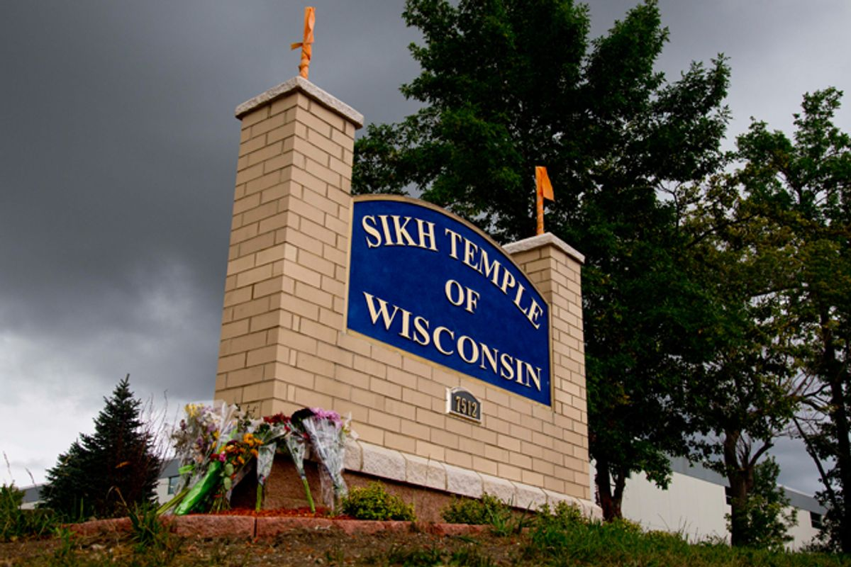 Flowers lie on the sign to the Sikh Temple of Wisconsin in Oak Creek. (AP/Jeffrey Phelps)