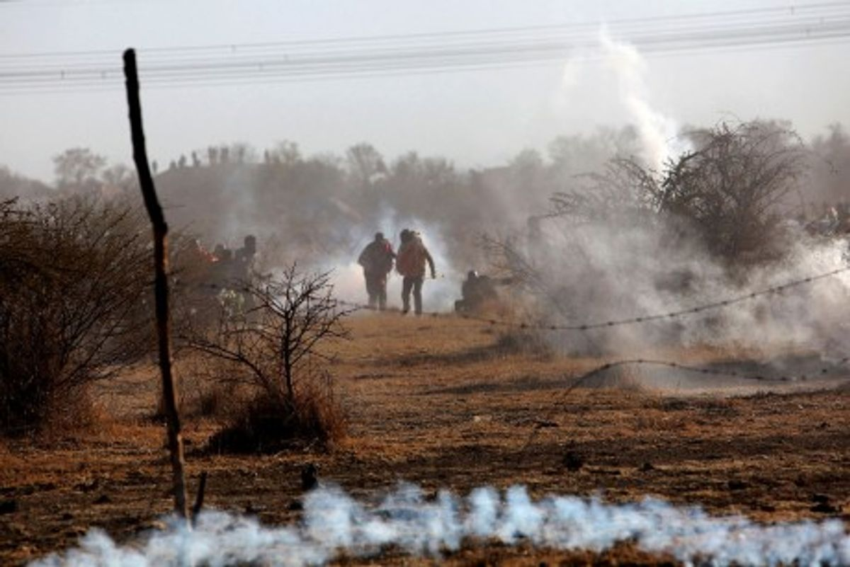 Striking mineworkers are caught in teargas as police open fire on striking miners at the Lonmin Platinum Mine near Rustenburg, South Africa, Thursday, Aug. 16, 2012. An unknown number of people have been killed and injured. Police moved in on workers who gathered on a rocky outcropping near the Lonmin late afternoon, firing unknown ammunition and teargas. (AP Photo) SOUTH AFRICA OUT(Credit: AP)