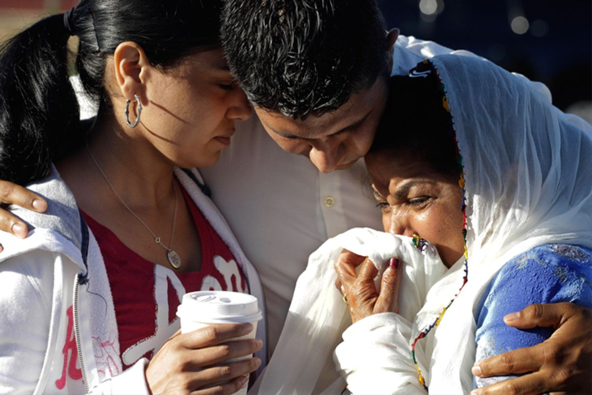 Amardeep Kaleka, son of the president of the Sikh Temple of Wisconsin, center, comforts members of the temple on Monday.        (AP/M. Spencer Green)