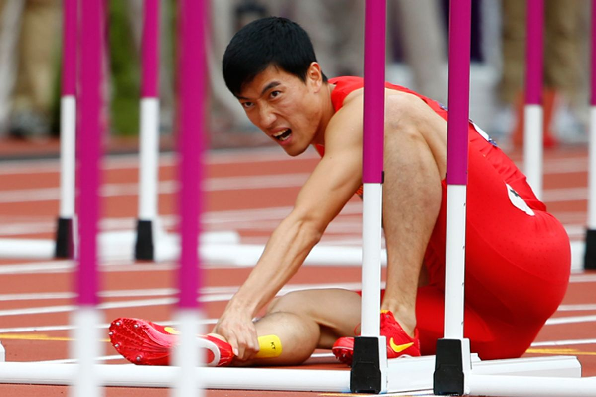Liu Xiang holds his leg after suffering an injury at the 2012 Olympic Games on Monday.     (Reuters/Kai Pfaffenbach)