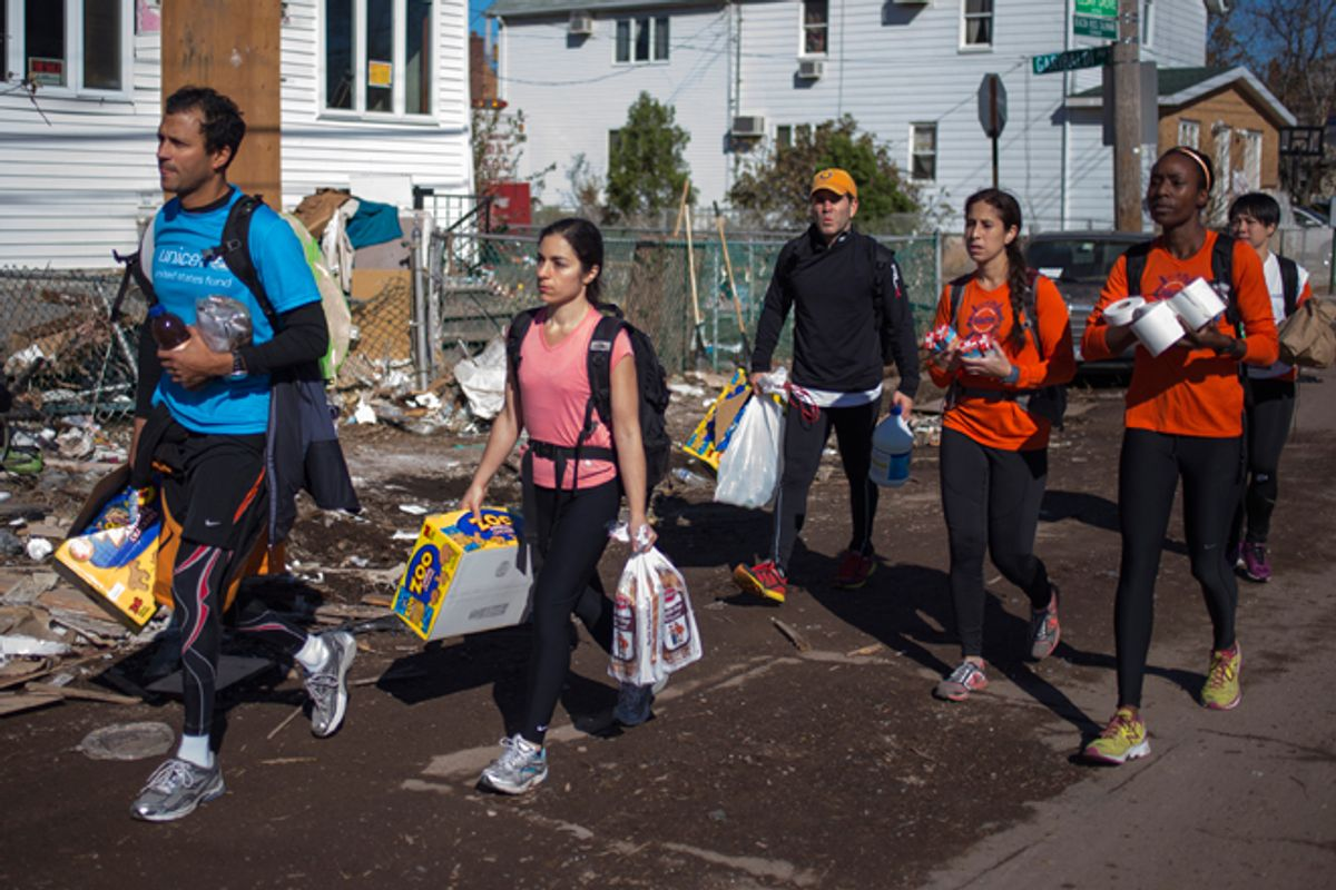 New York City Marathon runners carry relief supplies through a damaged neighborhood in Staten Island.       (Reuters/Adrees Latif)