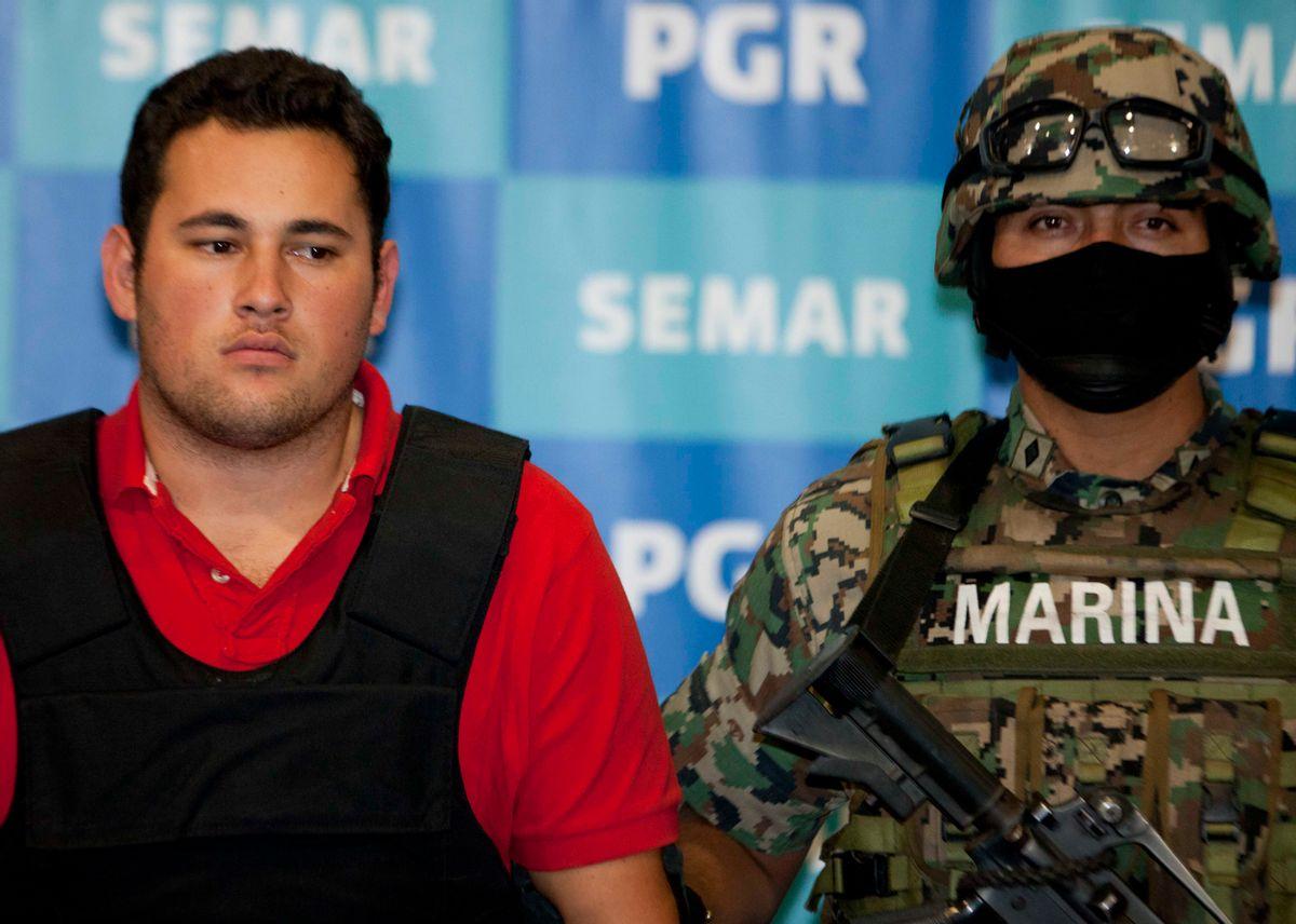 A Mexican marine escorts Jesus Alfredo Guzman Salazar, left, during his presentation to the media in Mexico City.                (AP/Eduardo Verdugo)
