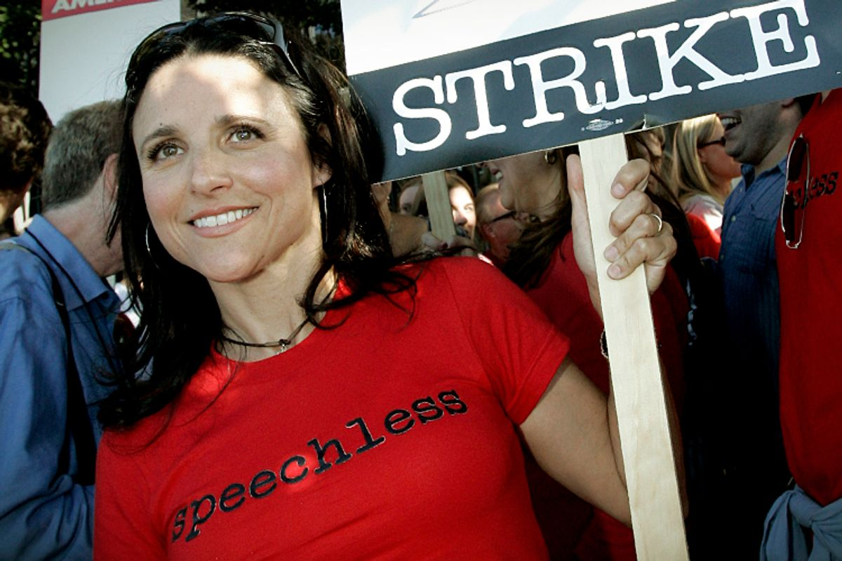 Screen Actors Guild (SAG) member Julia-Louis Dreyfus holds a strike sign  as she joins members of the Writers Guild of America (WGA) and others on the picket line.   (AP/Reed Saxon)