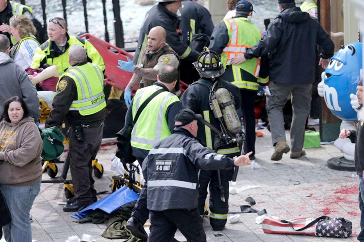 Medical workers aid injured people at the finish line of the 2013 Boston Marathon following an explosion in Boston, Monday, April 15, 2013.     (AP/Charles Krupa)