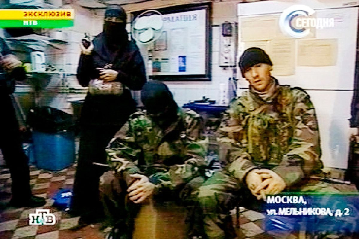 A man identified as Movsar Barayev, reported to be a leader of armed Chechens, who seized a crowded Moscow theater, right, is seen with another male captor, center, and a woman captor, left,  somewhere inside  the theater, Moscow, in this early Friday, Oct. 25, 2002 image from television by Russia's NTV.       (AP)